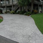 Stamped Concrete in in front of a large home flanked by green grass front yard