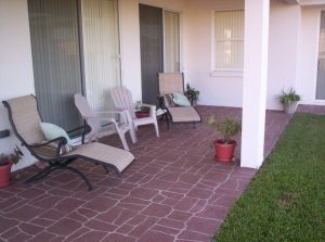 Comfortable back patio with patio furniture on stamped concrete