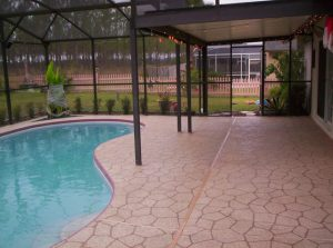 Enclosed pool with concrete pool deck sprayed using Spray Coat by Renew Crete