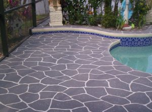 Enclosed pool deck with concrete spray pattern using gray and white grout lines