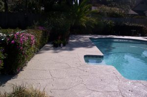 A concrete pool deck in the sunshine restored with Spray Coat by Renew Crete