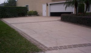 A concrete driveway leading to a garage door that is halfway open.