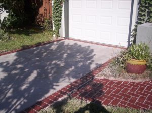 Spray coat on a small concrete driveway that is bordered with stenciled brick