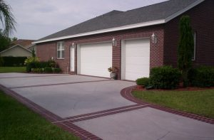 Spray Coat applied to a driveway with a red stenciled concrete border that complements the brick of the house.