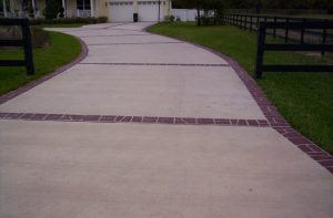 A long concrete driveway that leads up to a yellow house. The concrete is bordered with red stenciled concrete.