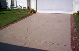 A light brown concrete driveway with a red border that has been sprayed with Spray Coat by Renew Crete