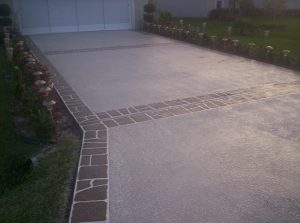 A driveway that has been restored using Spray Coat by Renew Crete and a border that has been stenciled to give a dynamic design.